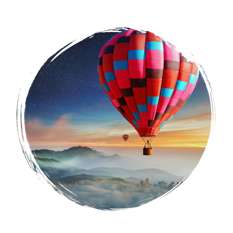 Adventure Travel - Hot Air Ballons Floating Over Mountains in Night Sky
